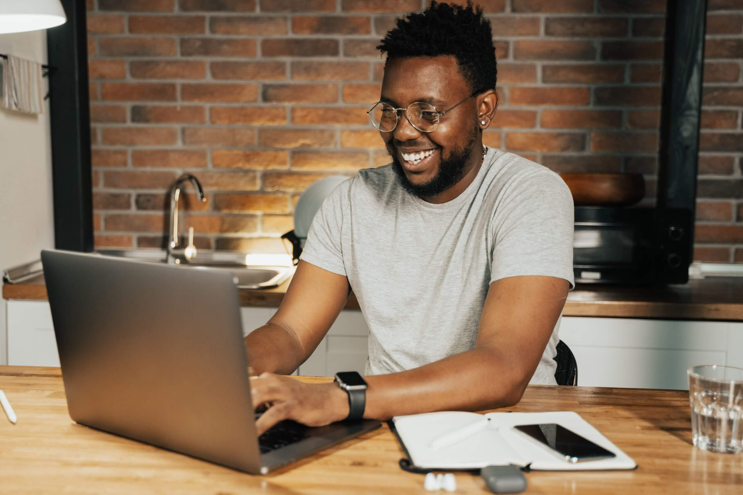 Happy black man working at a desk on his laptop