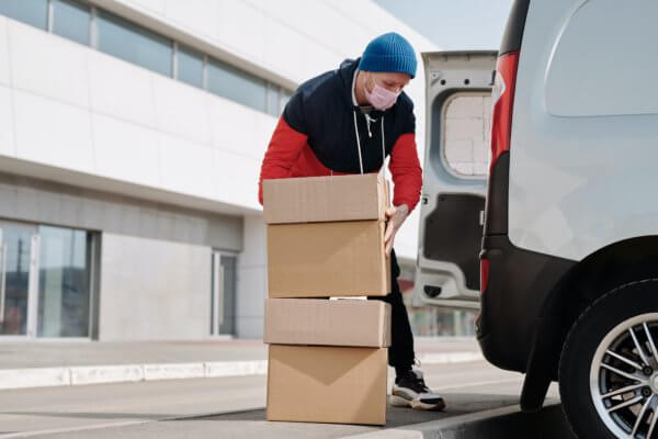 late dispatch, man carrying boxes into van, next day shipping, next day clothing, next day parcel delivery, next day courier service